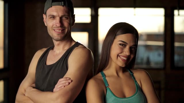 Portrait of smiling couple in the gym Portrait of smiling couple standing back to back in the gym and looking at camera. back to back stock videos & royalty-free footage