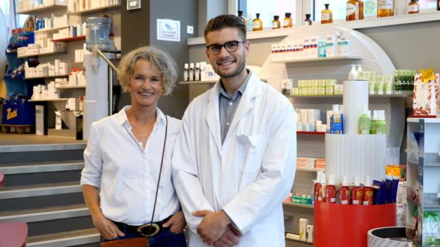 vidéos et rushes de portrait de sourire chimiste au magasin et le client - relation client