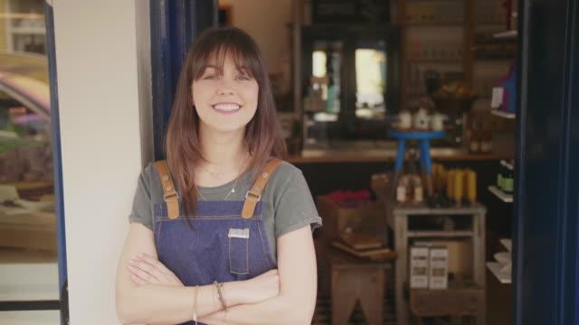 portret uśmiechniętego właściciela delikatesów, który stoi na zewnątrz sklepu - mały filmów i materiałów b-roll