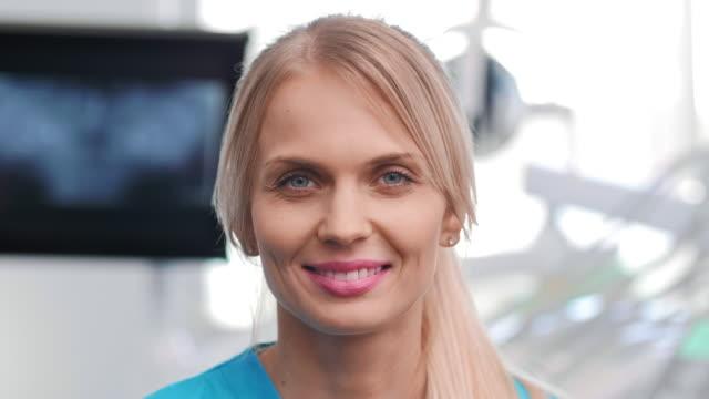 vídeos y material grabado en eventos de stock de retrato de un dentista sonriente en la clínica del dentista - ortodoncista