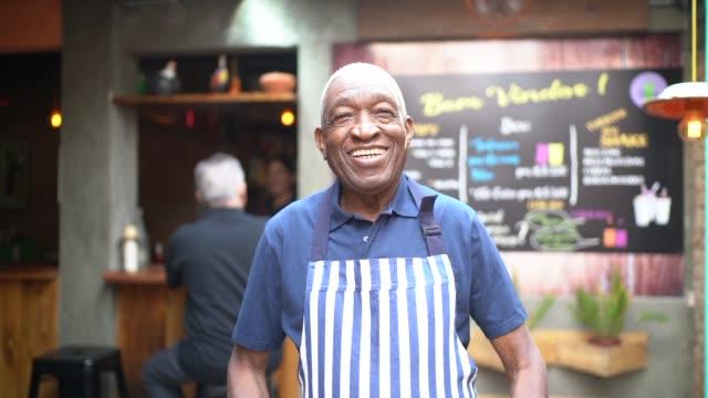 vídeos y material grabado en eventos de stock de retrato de camarero anciano sonriente mirando a la cámara - encuadre cintura para arriba
