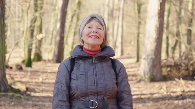 Portrait of smiling elderly woman hiking in forest