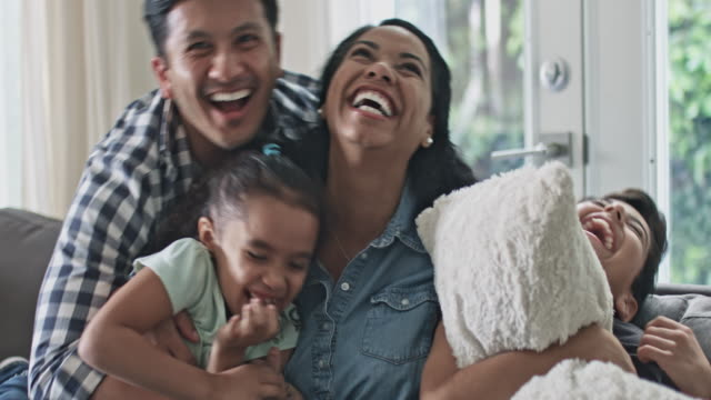 Portrait of smiling family having fun tickling in sofa at home Portrait of smiling multi-ethnic family. Father joins in the sofa with the family and start tickling everybody. hug stock videos & royalty-free footage