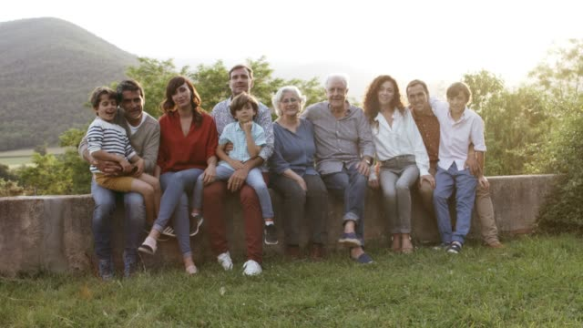 Portrait of smiling family sitting in yard
