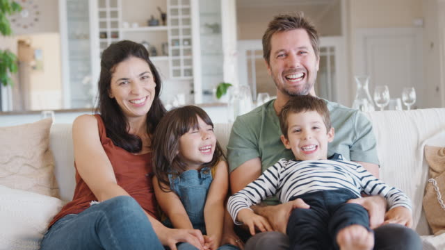 Portrait Of Smiling Family Sitting With On SofaÊ At Home Together