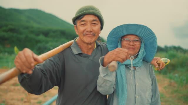 Portrait of smiling farm couple holding