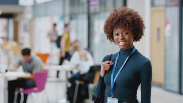 portrait of smiling female college student in busy communal campus building - badge video stock e b–roll