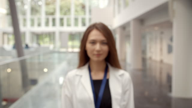Portrait Of Smiling Female Doctor In Lobby Of Hospital ビデオ