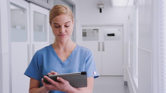 vídeos y material grabado en eventos de stock de retrato de una doctora mujer sonriente usando exfoliantes en el pasillo del hospital usando una tableta digital - encuadre cintura para arriba
