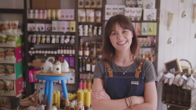 porträtt av leende kvinnliga ägare ständiga armar korsade i delikatessbutik - liten bildbanksvideor och videomaterial från bakom kulisserna