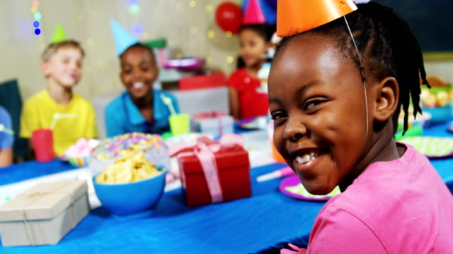 Portrait of smiling girl sitting with friends at table during birthday party 4k video