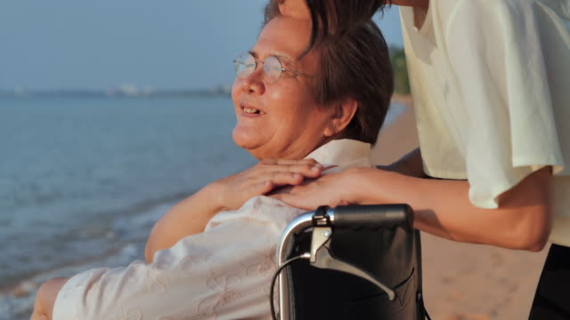 portrait of smiling happy asian senior mother with her adult daughter hugging on the beach.happy daughter is holding caregiver for a hand while spending time together.senior holidays,vacations,care,retirement,family concept,traveling with differing abilit - sostegno emotivo video stock e b–roll