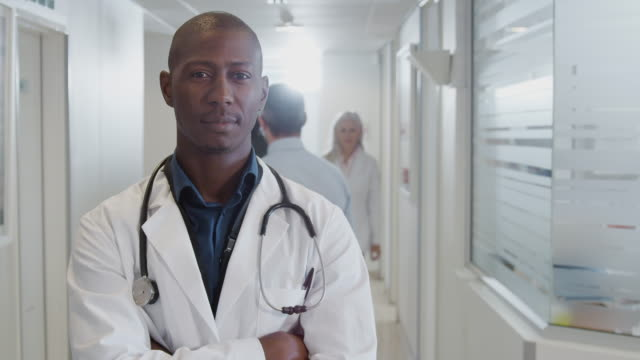 Portrait Of Smiling Male Doctor Wearing White Coat With Stethoscope In Busy Hospital Corridor Portrait of smiling male doctor wearing white lab coat standing in busy hospital corridor - shot in slow motion dermatology stock videos & royalty-free footage