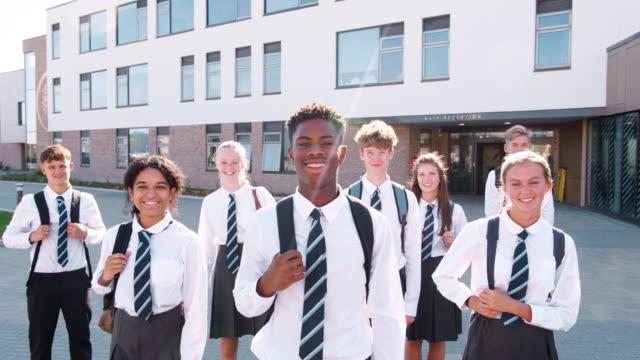 portret uśmiechniętych mężczyzn licealistów ubranych w mundurek na zewnątrz budynku college'u - uniform filmów i materiałów b-roll