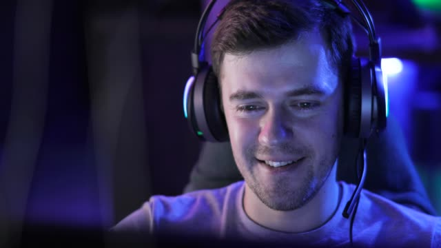 Portrait of smiling man gamer in headset talks with players plays game online Portrait of smiling man gamer in headset talking with players online and playing game on computer. Concept of relax and dependence on computer game. Online team gaming in network. Escape from reality. gamer stock videos & royalty-free footage
