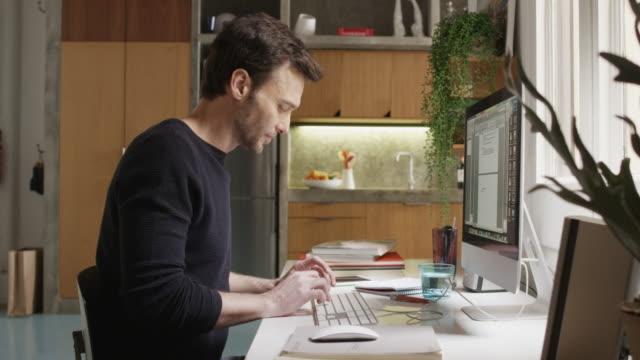 vídeos de stock e filmes b-roll de portrait of smiling man using computer at desk - teletrabalho