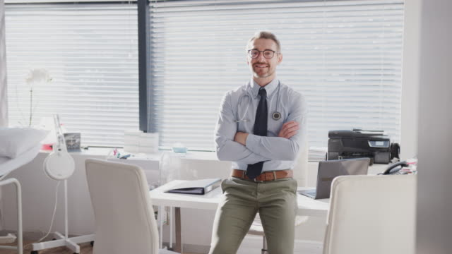 Portrait Of Smiling Mature Male Doctor Sitting On Desk In Office Portrait of mature male doctor sitting on desk and smiling at camera - shot in slow motion dermatology stock videos & royalty-free footage