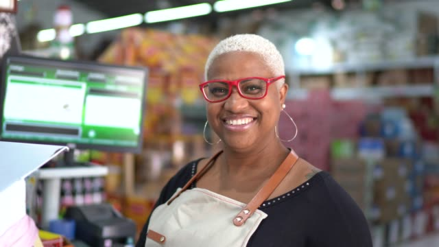 Portrait of smiling mature woman cashier at wholesale video