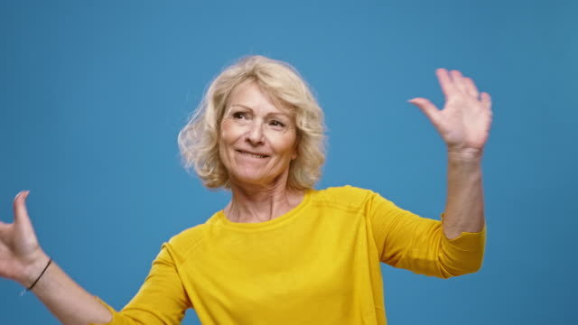 Portrait of Smiling Mature Woman having fun against a blue background Slow motion video of cheerful mature woman having fun against a blue background. background color stock videos & royalty-free footage