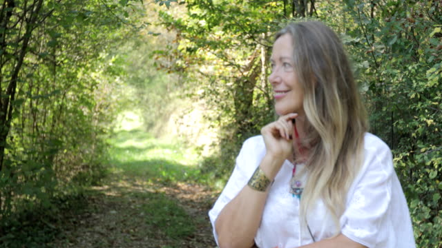 portrait of smiling mature woman in nature - woman portrait forest video stock e b–roll