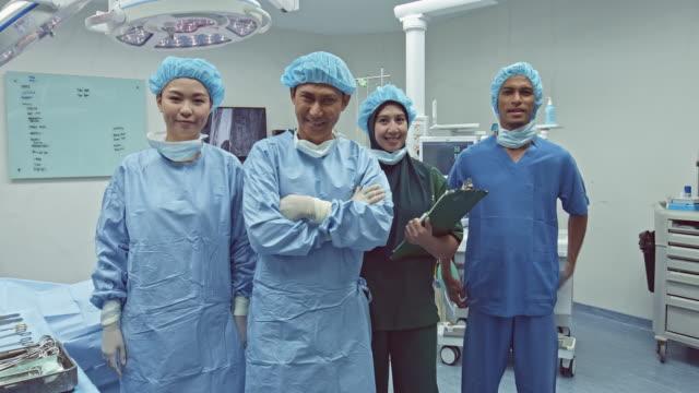 portrait of smiling medical team in the operating room - 30 39 lat filmów i materiałów b-roll