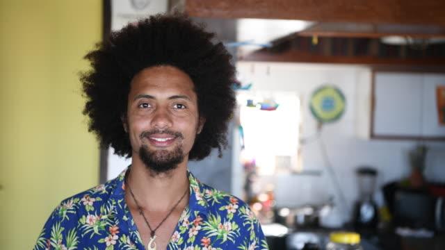 portrait of smiling mid adult brazilian man with afro hair - бразилец парду стоковые видео и кадры b-roll