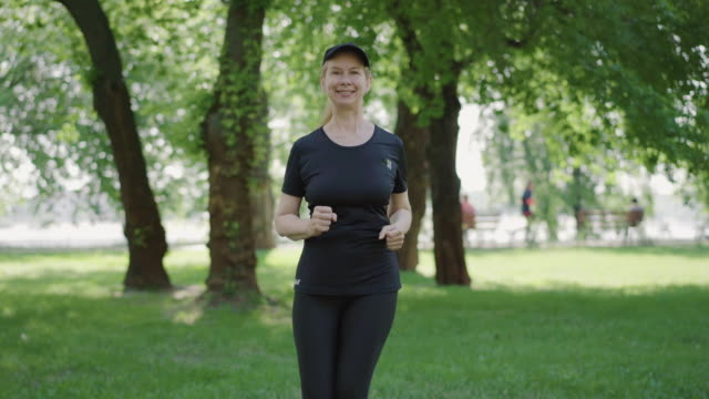 Portrait of smiling mid-adult sportswoman running in summer park and smiling at camera. Positive Caucasian woman in sportswear jogging outdoors on sunny day. Happy lady exercising on fresh air. Portrait of smiling mid-adult sportswoman running in summer park and smiling at camera. Positive Caucasian woman in sportswear jogging outdoors on sunny day. Happy lady exercising on fresh air. one mid adult woman only stock videos & royalty-free footage
