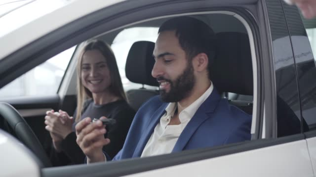 Portrait of smiling Middle Eastern man taking car keys from dealer and passing it to excited wife. Grateful spouse hugging handsome husband. Wealthy family sitting in new vehicle in showroom. Portrait of smiling Middle Eastern man taking car keys from dealer and passing it to excited wife. Grateful spouse hugging handsome husband. Wealthy family sitting in new vehicle in showroom. car key stock videos & royalty-free footage
