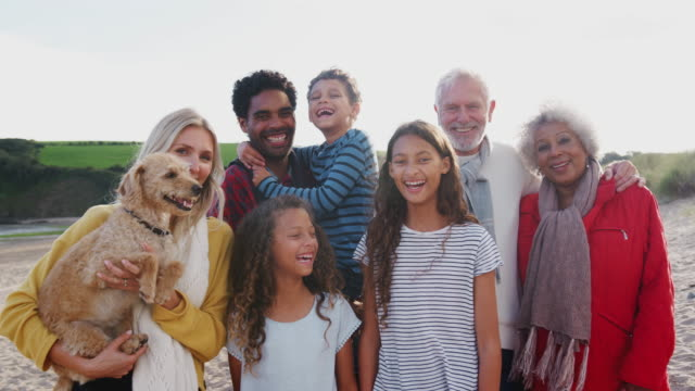 Portrait of smiling multi-generation family with pet dog on winter beach vacation - shot in slow motion