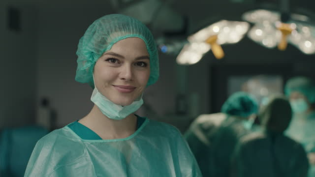 Portrait of smiling nurse in operating room Portrait of young smilin nurse in operating room in hospital nurse stock videos & royalty-free footage