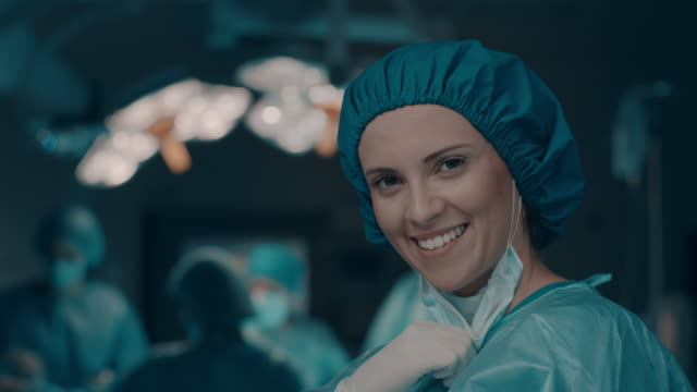 Portrait of smiling nurse taking off surgical mask video