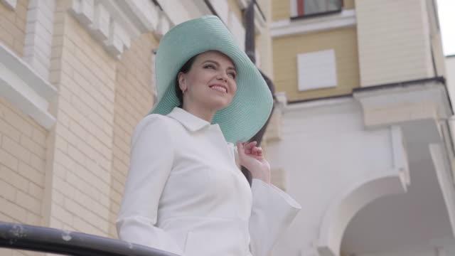 porträt der lächelnden positiven kaukasischen dame in elegantem mantel und hut stehen im freien in der stadt und wegschauen. mittlere aufnahme von eleganten charmanten frau genießen sonnigen tag. tourismus, reisen, freizeit. - einzelne frau über 30 stock-videos und b-roll-filmmaterial