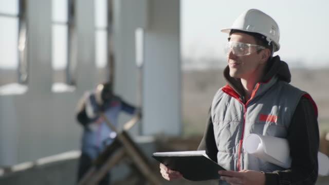 安全眼鏡とヘルメットを身に着けている保護服を着た笑顔のプロエンジニアの肖像画、溶接機の背景と溶接火花の大きな産業プラントの建設中 - 制服点の映像素材/bロール