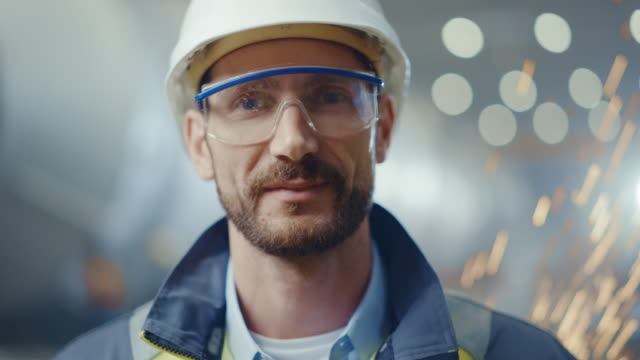 Portrait of Smiling Professional Heavy Industry Engineer / Worker Wearing Safety Uniform, Goggles and Hard Hat. In the Background Unfocused Large Industrial Factory where Welding Sparks Flying
