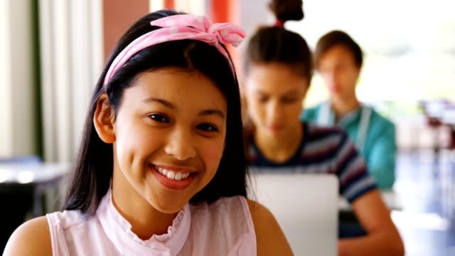 Portrait of smiling schoolgirl studying in classroom video