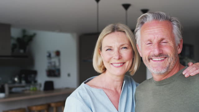 Portrait Of Smiling Senior Couple Standing In Kitchen Together Handheld gimbal portrait of senior couple standing in kitchen and talking together - shot in slow motion contented emotion stock videos & royalty-free footage