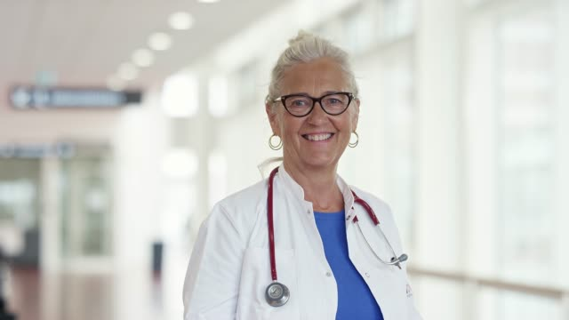 Portrait of smiling senior healthcare worker Portrait of smiling senior female professional. Handheld shot of confident female doctor is standing at hospital. She is wearing lab coat. general practitioner stock videos & royalty-free footage