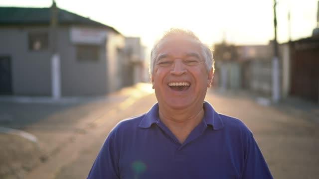vídeos de stock, filmes e b-roll de retrato do homem sênior de sorriso que olha a câmera na rua - sul europeu