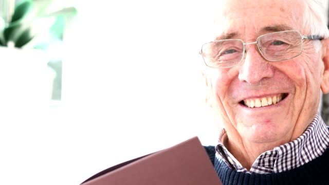Portrait Of Smiling Senior Man Reading Book At Home video