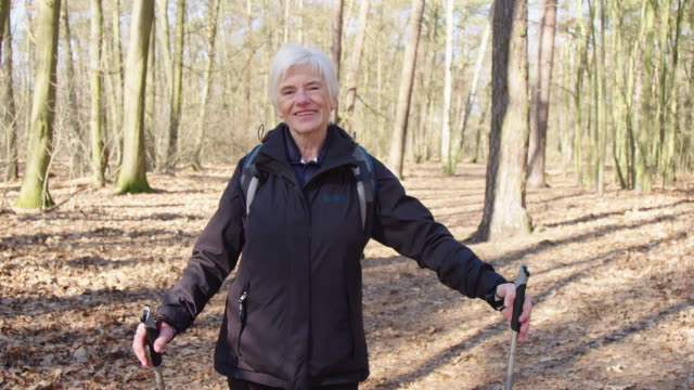 Portrait of smiling senior woman hiking in forest