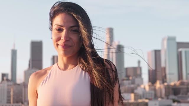 테라스에 웃는 스포티 한 여자의 초상화 - 몸매 관심 스톡 비디오 및 b-롤 화면