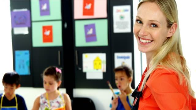 笑顔の先生がクラスを描画で schoolkid を支援の肖像画 - 美術の授業点の映像素材/bロール