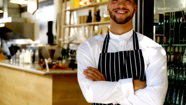 vídeos de stock e filmes b-roll de portrait of smiling waiter standing with arms crossed 4k - avental