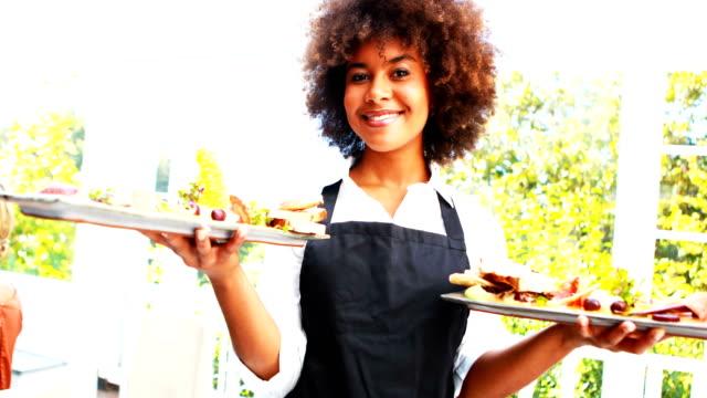 Portrait of smiling waitress holding food tray