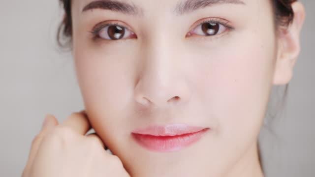 vídeos y material grabado en eventos de stock de retrato de mujer sonriente aplicando crema facial. - feminidad