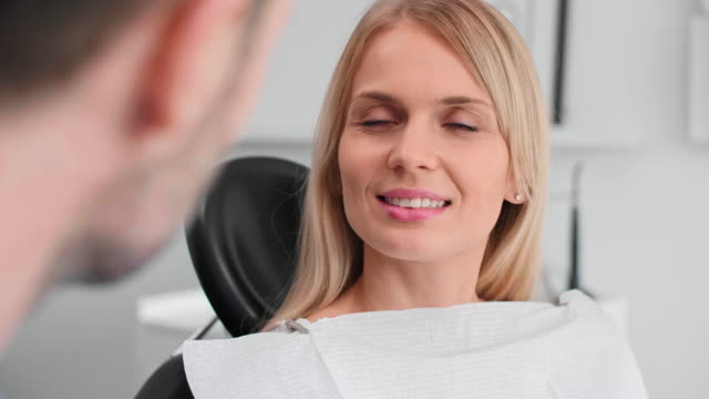 portrait of smiling woman at the dentist's office - dentist стоковые видео и кадры b-roll