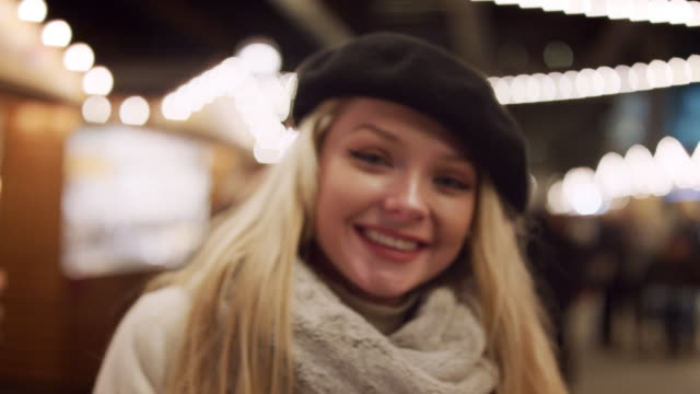 Portrait Of Smiling Woman Enjoying Christmas Market At Night video