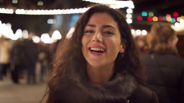 Portrait Of Smiling Woman Enjoying Christmas Market At Night Portrait Of Smiling Woman Enjoying Christmas Market At Night carnival celebration event stock videos & royalty-free footage