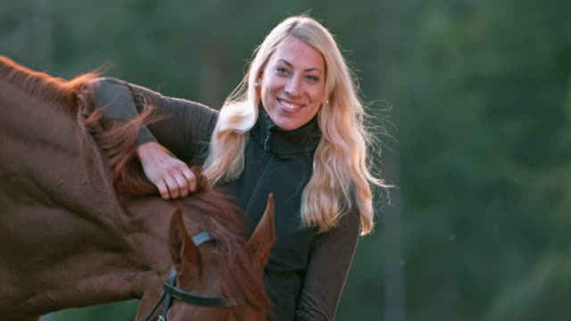 SLO MO Portrait of smiling woman petting her horse