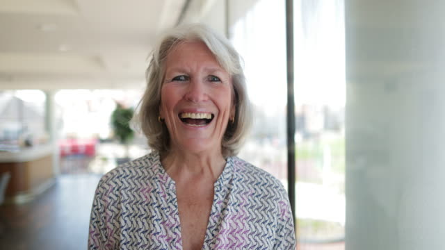 Portrait Of Smiling Woman A portrait video of a cheerful smiling woman looking to camera with positive emotion. human age stock videos & royalty-free footage
